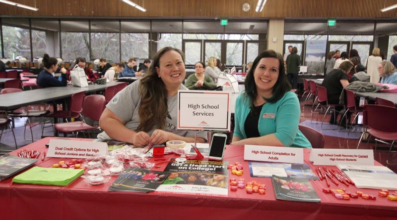 CONTRIBUTED PHOTO: MHCC - Two college staffers ready their table for the Mt. Hood Community College Preview Day, which is a chance for potential students to learn about the school.