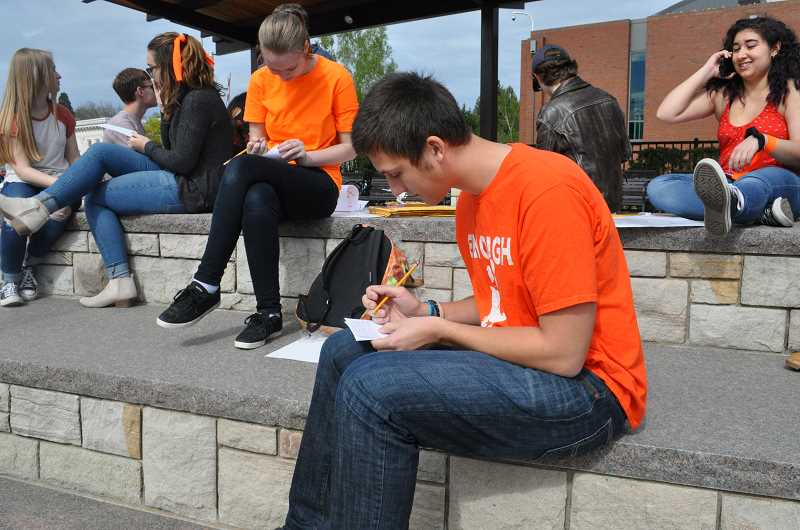 GAZETTE PHOTO: BLAIR STENVICK - Matthew Schantin of Sherwood High writes a letter to a local lawmaker in support of stricter gun control legislation.