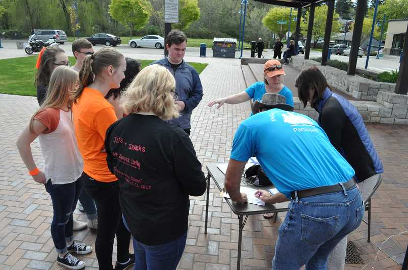 GAZETTE PHOTO: BLAIR STENVICK - Members of Our Indivisible Revolution Sherwood help students register to vote in Cannery Square.