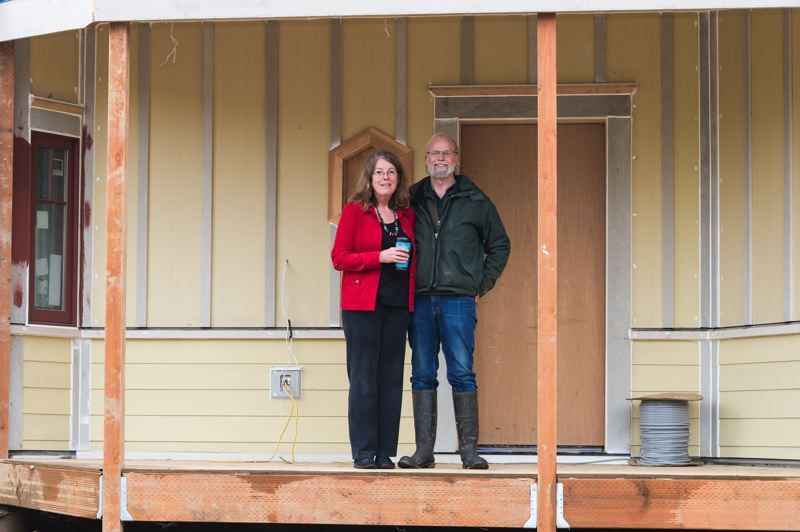 STAFF PHOTO: CHRISTOPHER OERTELL - Linda and Brad Taylor stand on the front porch of their new home in the Green Grove Cohousing Community, a housing cooperative they are developing on a five-acre property in Forest Grove.