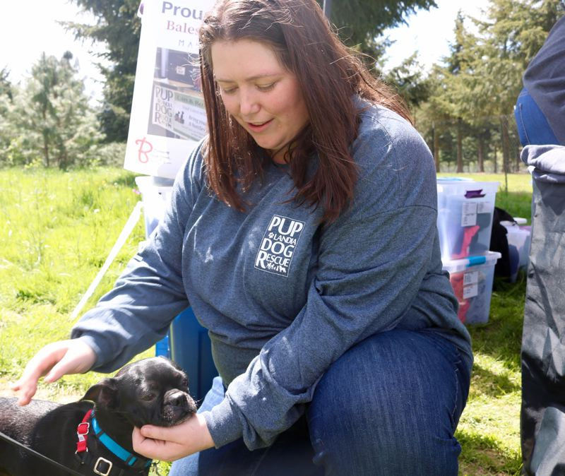 VALLEY TIMES PHOTO: ZANE SPARLING - Brook Benson, 32, pats a puppy during the two-year birthday party for her organization, Puplandia Dog Rescue, on Saturday, April 21.