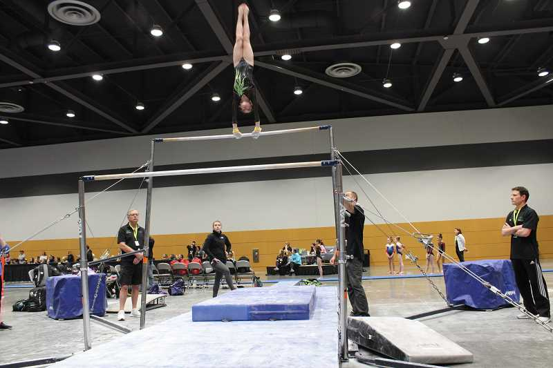 SUBMITTED PHOTO - Piper Colby, 13, swings around on the uneven bar during one of her meets. Colby has qualified to participated in a national gymnastics meet in Salt Lake City on May 4.
