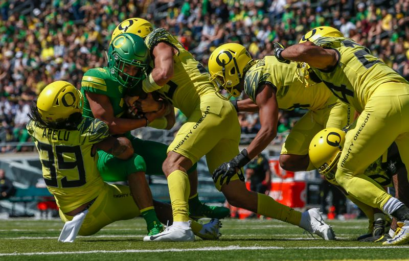 COURTESY: ANDY NELSON/THE REGISTER-GUARD - Running back Travis Dye is stopped by Kaulana Apelu, Troy Dye, Thomas Graham Jr. and Keith Simms during the Oregon Spring Game at Autzen Stadium on Saturday.