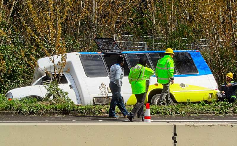 ERIC NORBERG - TriMet personnel look over their LIFT bus, stuck in a ditch northbound along S.E. McLoughlin Boulevard.