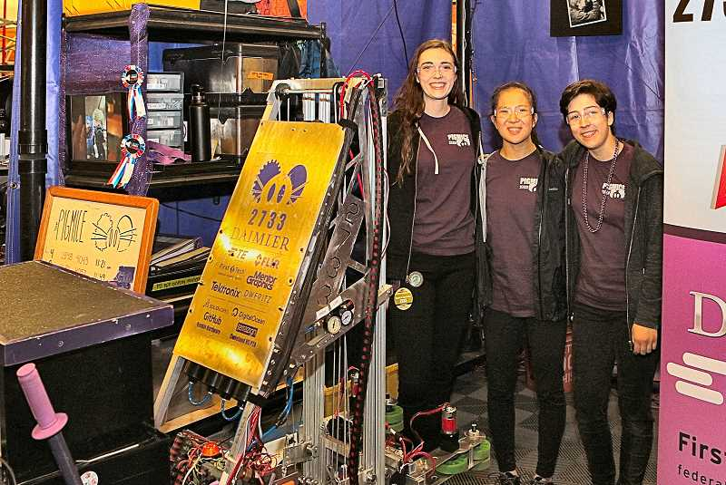 DAVID F. ASHTON - Pigmice computer-aided-engineering lead Isabelle Rinehart, programming team member Chrisse Hung, and programming team captain Flora Abrams, stand with their robot in the pit area.