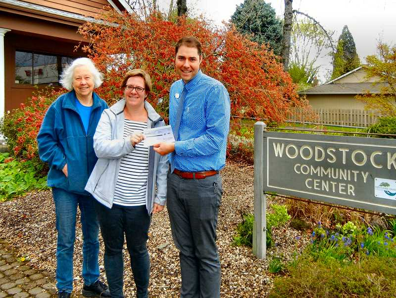 ELIZABETH USSHER GROFF - Terry Griffiths, left, one of the founders of Friends of the Woodstock Community Center, accompanies FWCC Chairperson Dawn Haecker in receiving a $3,235 check from Matt Civis, Woodstock Advantis Credit Union Manager, as part of the grand opening promotion.
