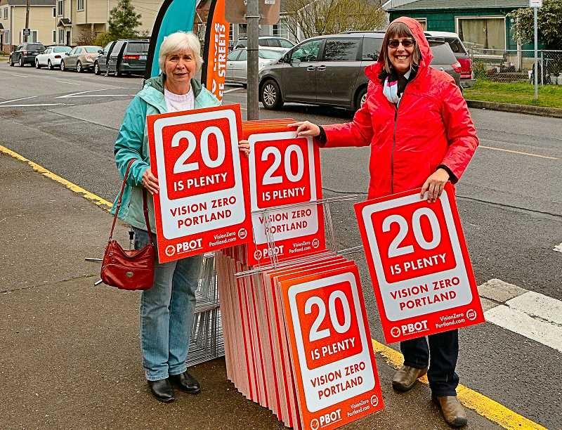 DAVID F. ASHTON - Sellwood resident Jan Hainley picks up a 20 is Plenty sign from Portland Bureau of Transportation staffer Sharon White, at Lane Middle School.