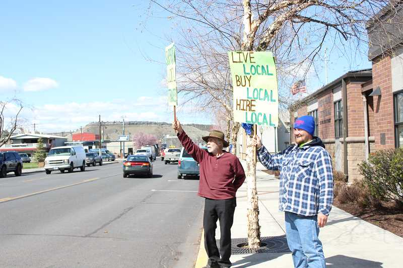 JASON CHANEY/CENTRAL OREGONIAN   - Hermilof Estrada Sr., left, and Jon Nortz hold signs that, at first glance, would lead passers-by to believe they were promoting shopping local. In fact, they are protesting out-of-state ironworkers hired by Facebook.