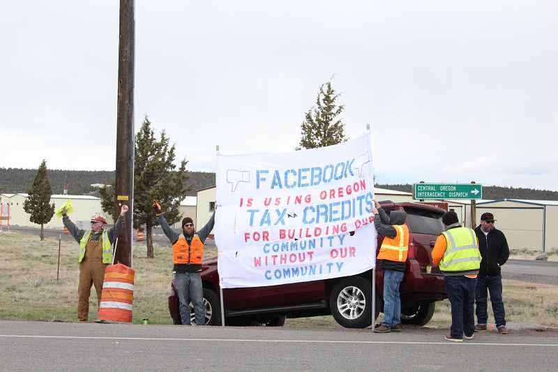 JASON CHANEY/CENTRAL OREGONIAN  - Picketers from Pacific Northwest Ironworkers District Council and local men out of work stand along Highway 126 last week, questioning whether or not the social media giant seeks local contractors to build in Oregon.