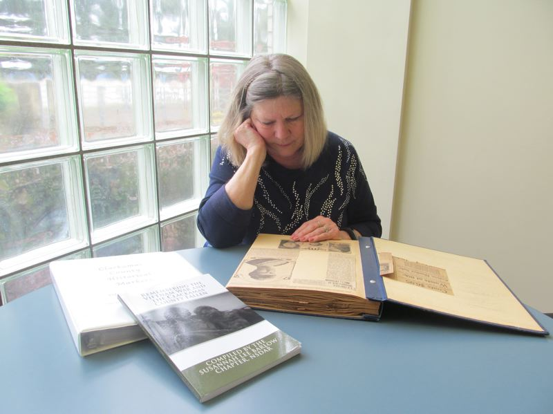 PHOTO BY ELLEN SPITALERI - Phyllis Hines, regent of the Susannah Lee Barlow Chapter of the DAR, reviews a scrapbook filled with stories about the groups activities in the early days of its formation.