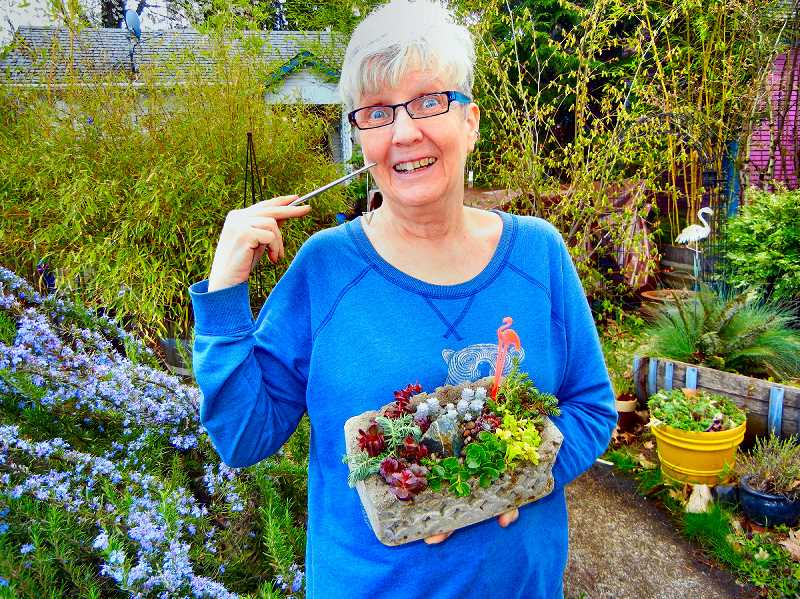 ELIZABETH USSHER GROFF - Hypertufa Queen Shelly Keach uses a metal chopstick, pictured, to delicately arrange sedum in hypertufa garden pots made by Woodstock neighbors. They are sold at the annual plant sale the day before Mothers Day which supports the Woodstock Community Center.