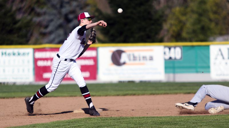 TIMES PHOTO: DAN BROOD - Sherwood junior second baseman Tyler Hix makes a throw to first base after forcing out Tualatins Cole Kinman at second.