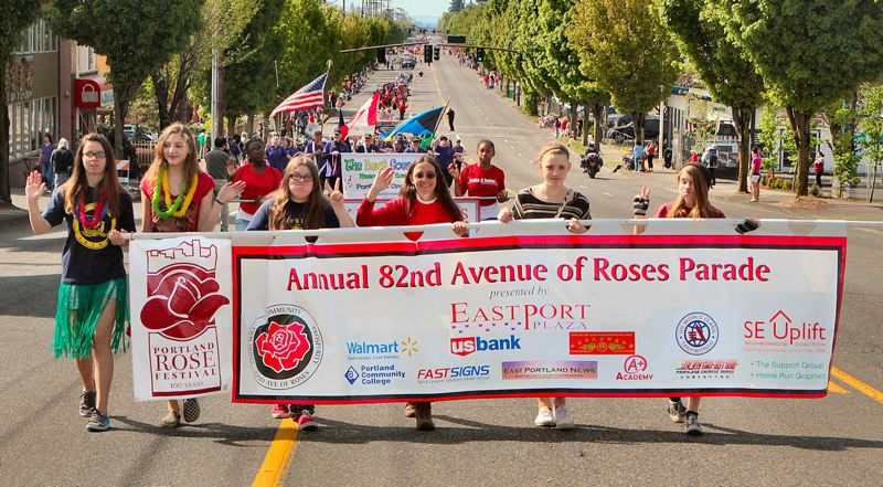 PORTLAND TRIBUNE FILE PHOTO - Volunteers carry the banner that signals the start of the 2013's 82nd Avenue of Roses Parade. After a hiatus in 2017, the parade is returning this year.