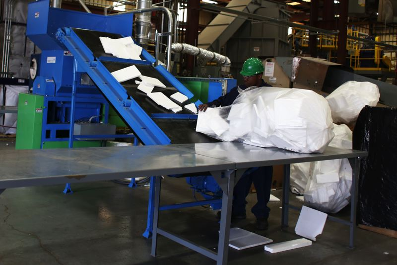 JESSIE DARLAND - Bags of Styrofoam are pushed through a machine to condense the material at Agilyxs facility in Tigard.