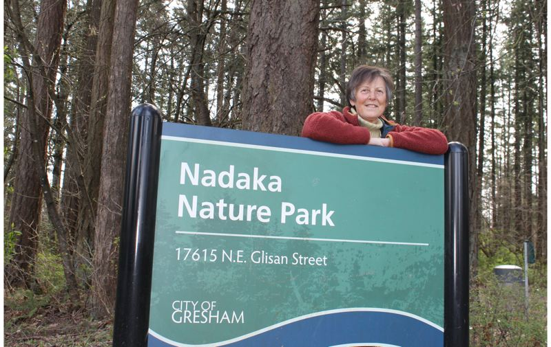 PAMPLIN MEDIA PHOTO: ANNE ENDICOTT - East Multnomah County resident Lee Dayfield stands with an entrance sign to the nature park she moved heaven and earth to help build. The site had been a day camp owned by Camp Fire of Columbia for nearly 40 years before the city of Gresham purchased the property in 1995.