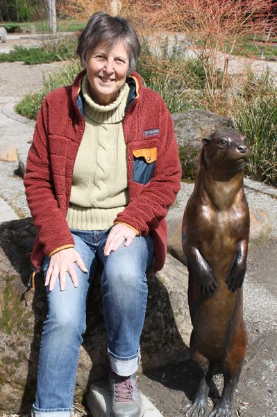 PAMPLIN MEDIA PHOTO: ANNE ENDICOTT - Dayfield sits with 'Slider,' a bronze otter designed by Troutdale sculptor Rip Caswell and placed in Nadaka Nature by the Gresham Public Art Committee.