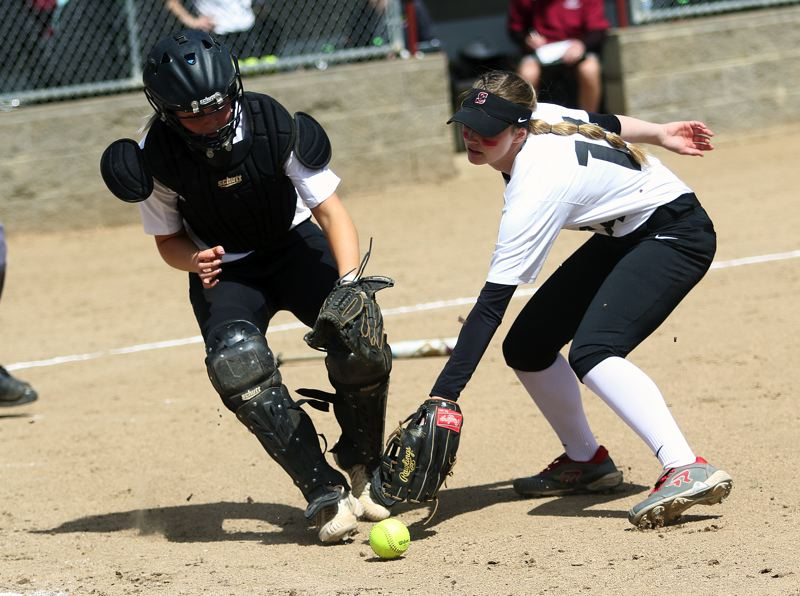 TIMES PHOTO: DAN BROOD - Sherwood senior catcher Emily Watson (left) and sophomore first baseman Olivia Dirks reach for a bunted ball during Saturday's game.
