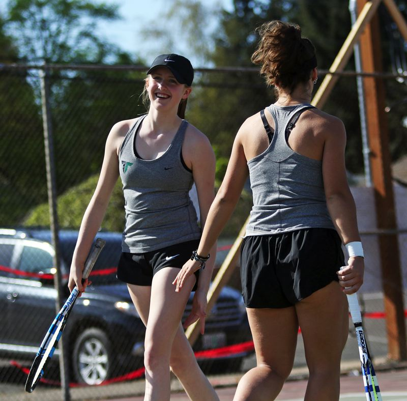 TIMES PHOTO: DAN BROOD - Tigard High School freshman Ali Dreves (left) and junior Nicole Mazzeo are all smiles during their No. 1 doubles match against Sherwood.