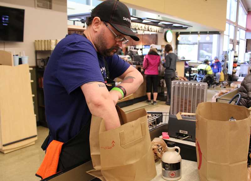 REVIEW PHOTO: SAM STITES - Richie Gensman helps a customer bag her groceries at the Safeway store in downtown Lake Oswego.