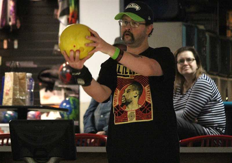 REVIEW PHOTO: SAM STITES - Richie Gensman takes aim at Tigard Bowl. He uses the markings on the floor to line up before each frame. His girlfriend, Erica Buchanan, watches in the background.