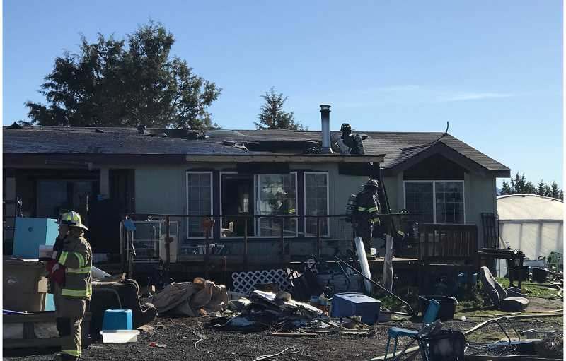 SUBMITTED PHOTO - Crooked River Ranch firefighters continue to work to ensure that a fire in a manufactured home is completely out.