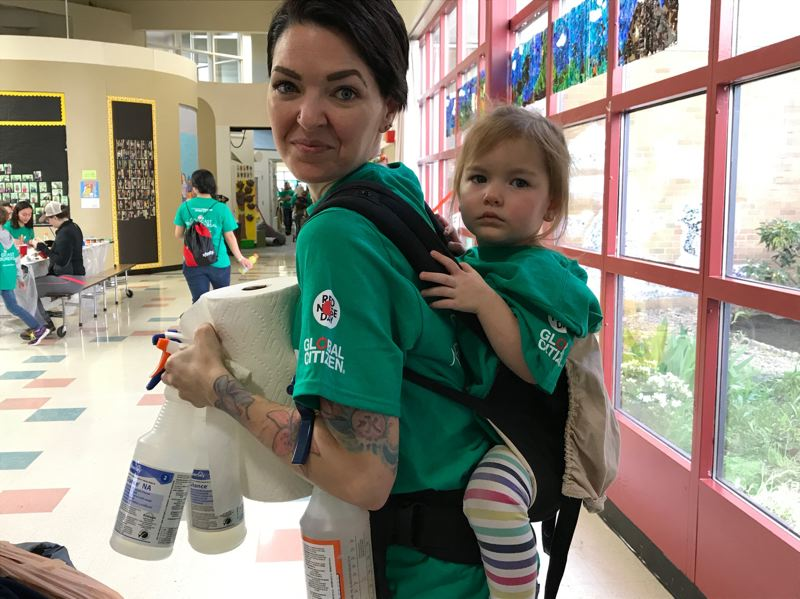 CONTRIBUTED PHOTO: COMCAST  - 5. Crystal Cline of Troutdale, a local parent with Riyen on her back, ready to tackle another job at Comcast Cares Day.