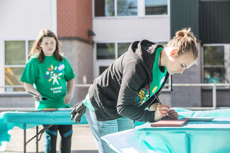 TIMES PHOTO: JONATHAN HOUSE - Ulla Braaten helps paint signs during Comcast Cares Day at Metzger Elementary.