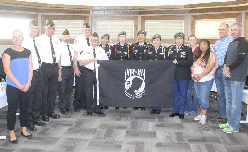 SUSAN MATHENY - Madras High School JROTC cadets accepted a missing in action/prisoner of war flag from VFW Post 12141 at the April 23 meeting of the 509-J School District Board of Directors.