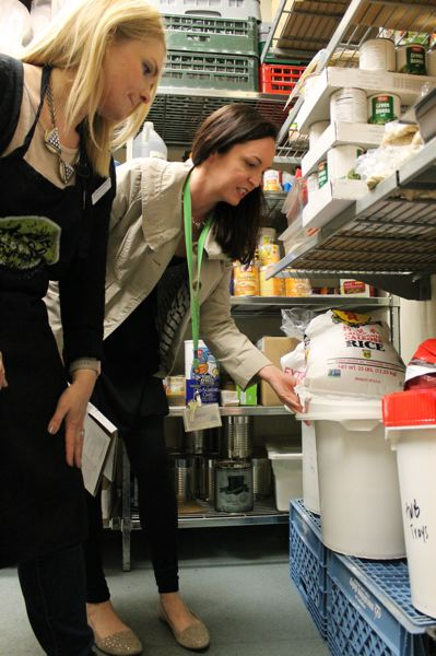 OUTLOOK PHOTO: ANNE ENDICOTT - In the center's storage room, Bigham consults with dietetic intern Jennifer Schaffer to make sure the bulk foods on hand meet nutritional standards.