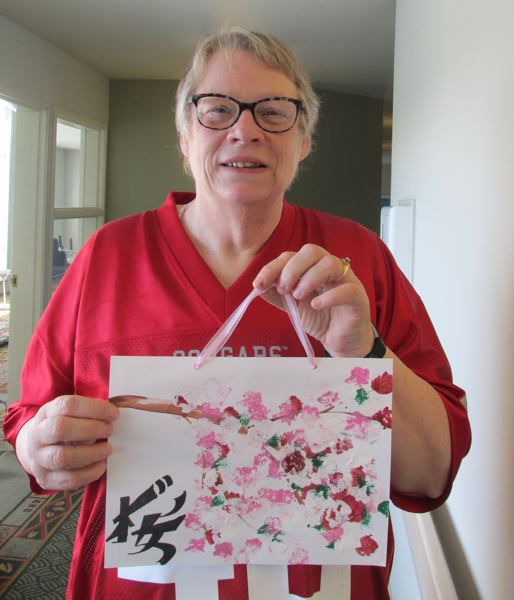 OUTLOOK PHOTO: TERESA CARSON - Morris shows off an example of a recent painting she taught other residents at the assisted living facility.