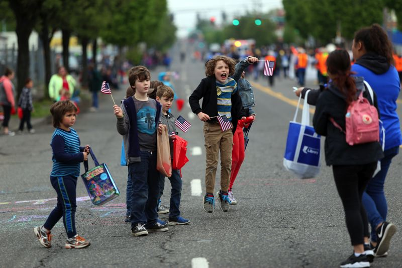 JESSIE DARLAND - Kids jump and cheer as parade marchers approach them with handfulls of candy.
