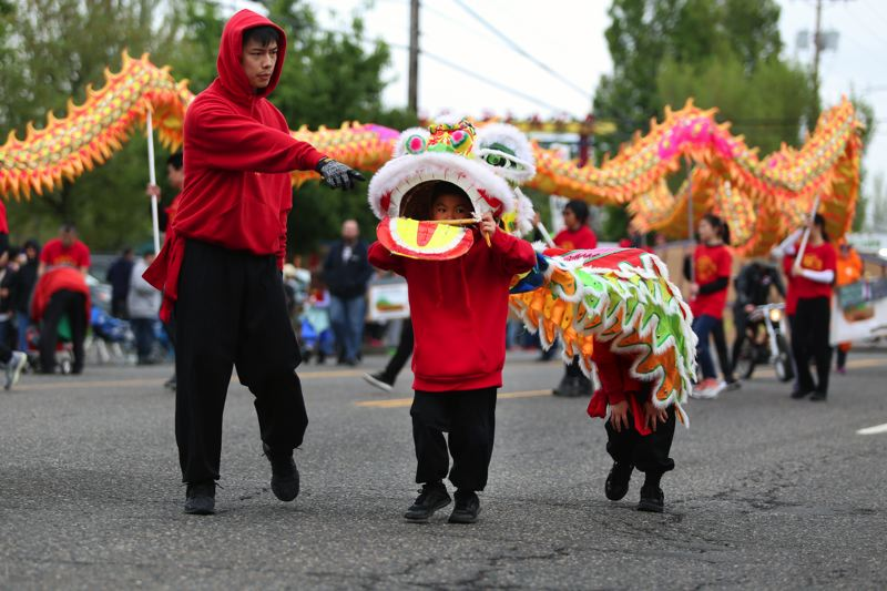 JESSIE DARLAND - Children march through the parade with the Chinese Dragon in their own little dragon.
