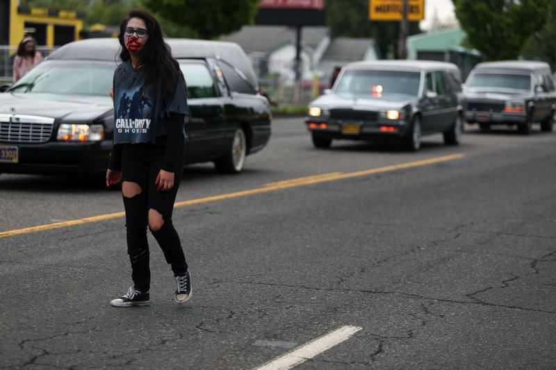 JESSIE DARLAND - A zombie scuffles past with a line of hearses, brought by the Coffin Cruisers Hearse Club.