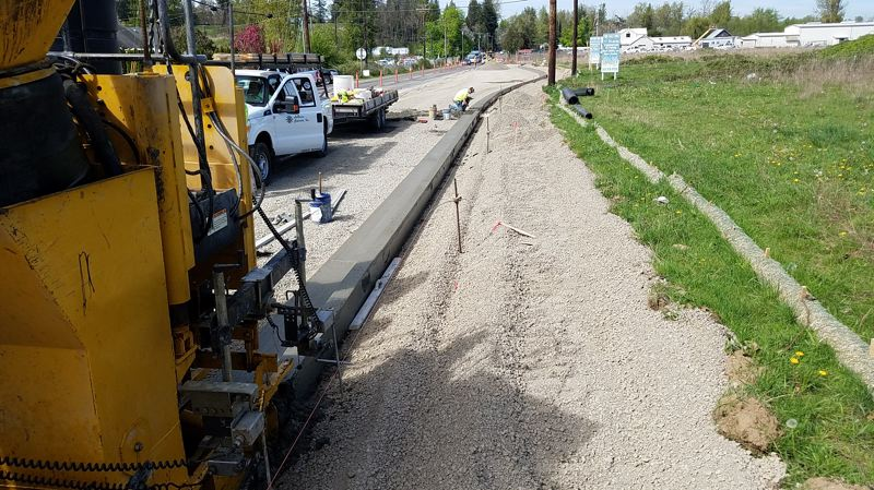 CONTRIBUTED PHOTO - Workers are shown here constructing a new curb on Northeast Sandy Boulevard in Wood Village on Friday, April 20.