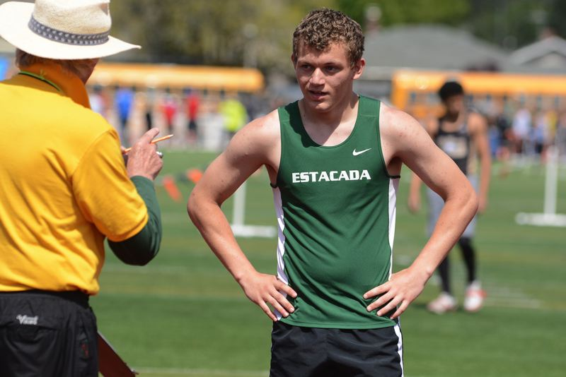 ESTACADA NEWS: DAVID BALL - Estacadas Logan Stamm checks in with an event official while juggling the high jump and the long jump which were taking place at the same time at Saturdays Dick Baker Invitational.