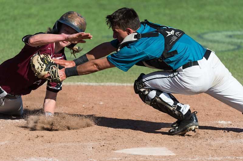 STAFF PHOTO: CHRISTOPHER OERTELL - Century catcher Alex Garcia tags Glencoe's Nathan Sprenger out at the plate during the Jags' game with the Tide April 26, at Ron Tonkin Field.