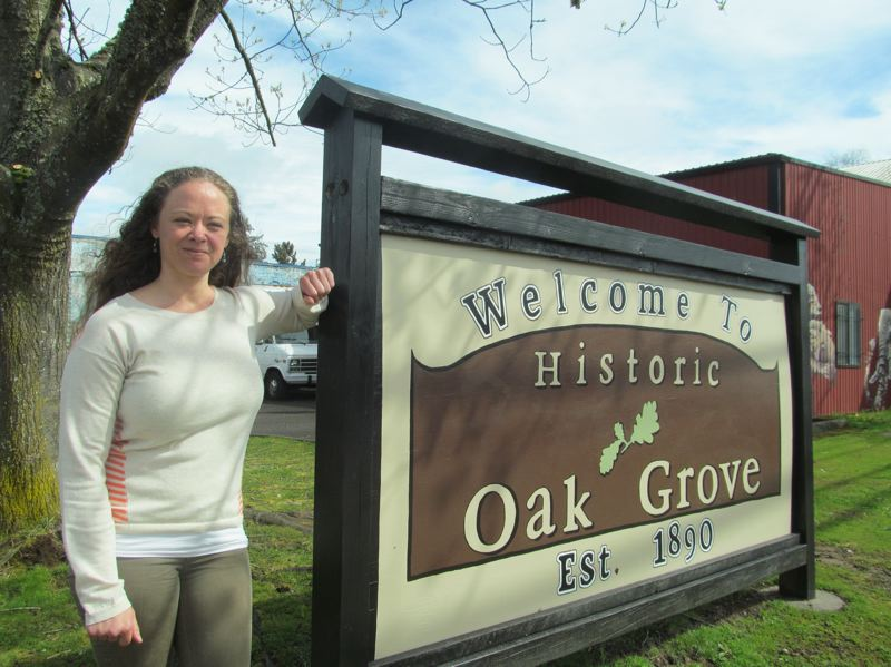 PHOTO BY DICK TRTEK - Fallon Kraxberger stands by the new 'historic Oak Grove' sign painted by local artist Sarah Shay.