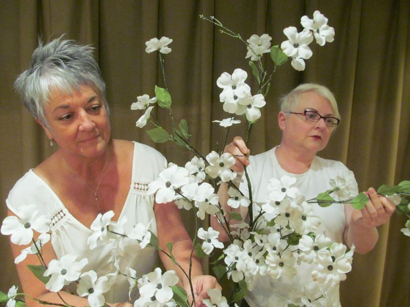 PHOTO BY DICK TRTEK - From left, Mary Weigel (Lucille) and director Julie Akers arrange flowers to be used in Act 2 of 'The Cemetery Club.'