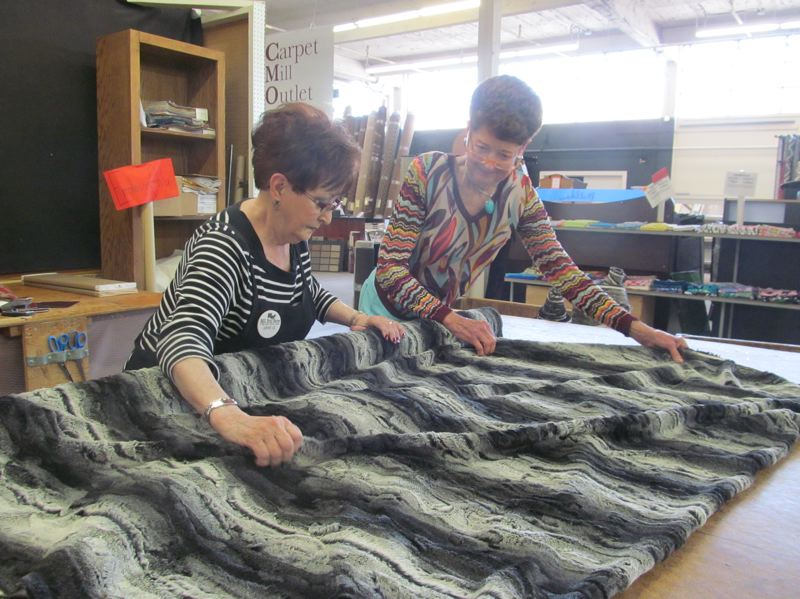 PHOTO BY ELLEN SPITALERI - Longtime Mill End employee Jane Quinn, left, and store owner Nancy Bishop Dietrich admire some plushy fabric on one of the Milwaukie stores cutting tables.