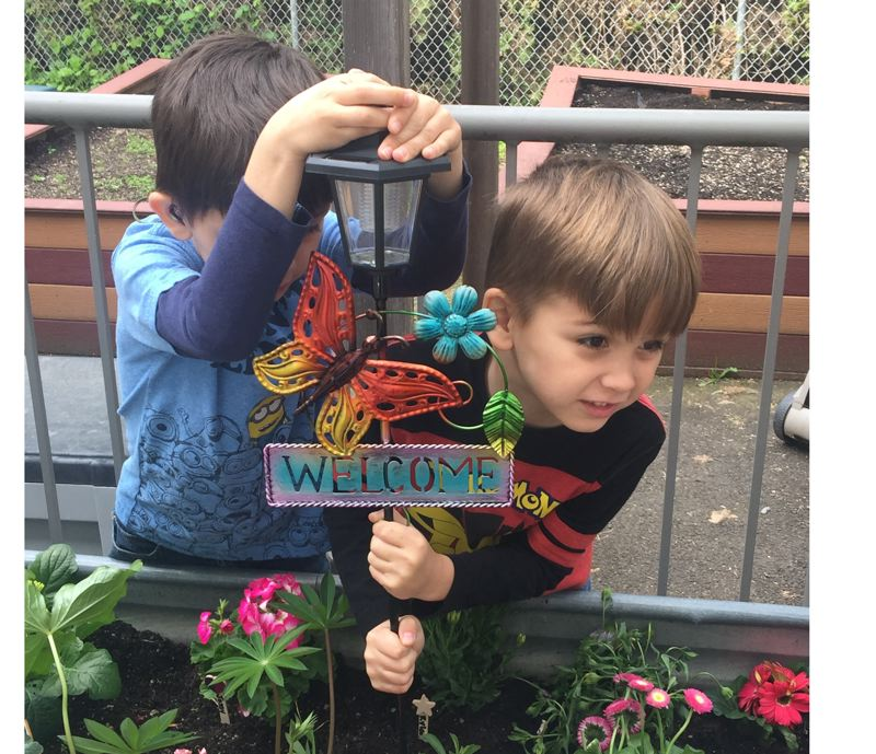 PHOTO COURTESY: LESLIE ROBINETTE - Twins Aiden and Jaxson Cule add the finishing touch to the butterfly garden at the Gladstone Center for Children & Families.