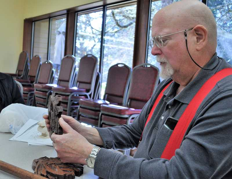 GAZETTE PHOTO: BLAIR STENVICK - Alan Pearson examines one of his hand-carved wooden art pieces.