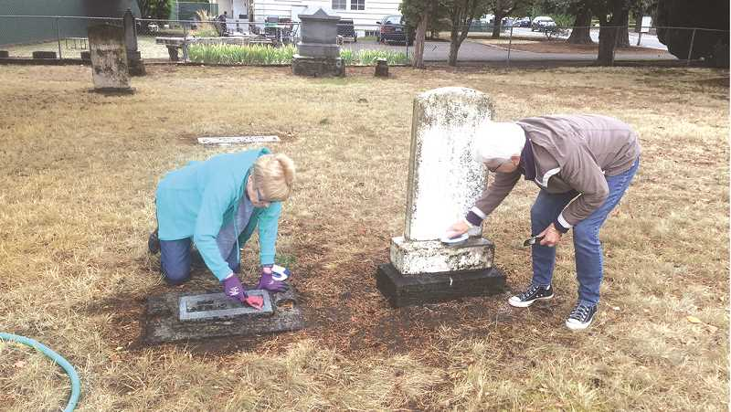 Carol Palmer and Pam Judy clean markers at Baker Prairie Cemetery in 2017.