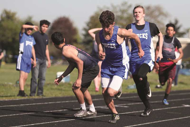 PHIL HAWKINS - St. Paul's Jaidyn Jackson (middle) and Jaden Thompson (behind right) form one half of the Buckaroos' 4x100 relay team that beat the league-leading Regis Rams by 0.02 seconds at the Bucks' home track meet on Thursday.