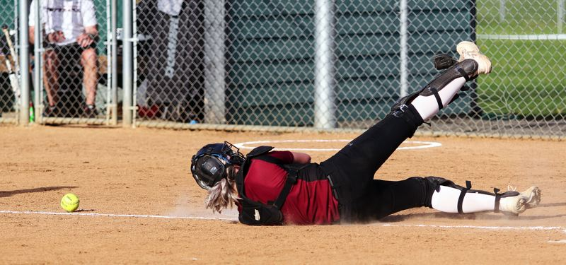TIMES PHOTO: DAN BROOD - Sherwood senior catcher Emily Watson dives out in an attempt to get a bunted ball during the Three Rivers League game at Tigard.