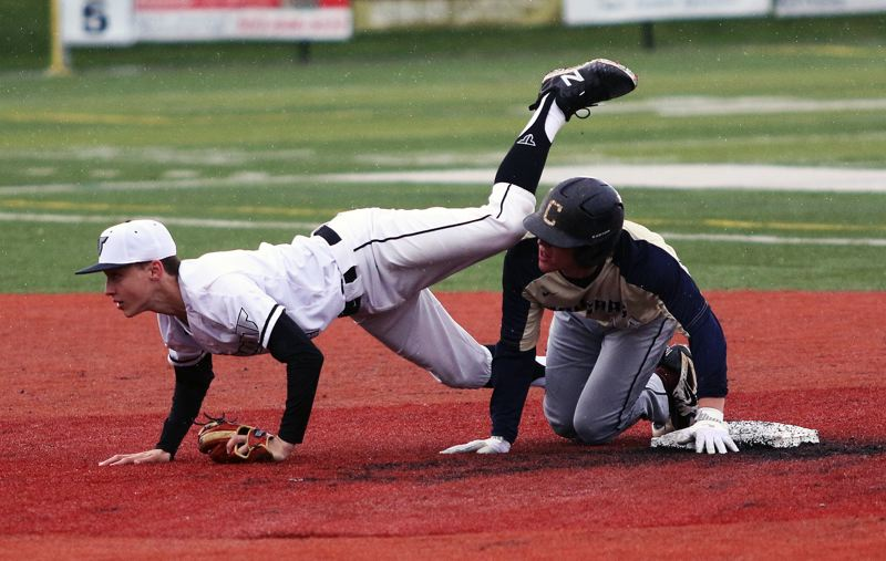 TIMES PHOTO: DAN BROOD - Tigard sophomore second baseman Ethan Clark (left) stumbles over Canbys Kenneth Tro after tagging him out during Fridays game.