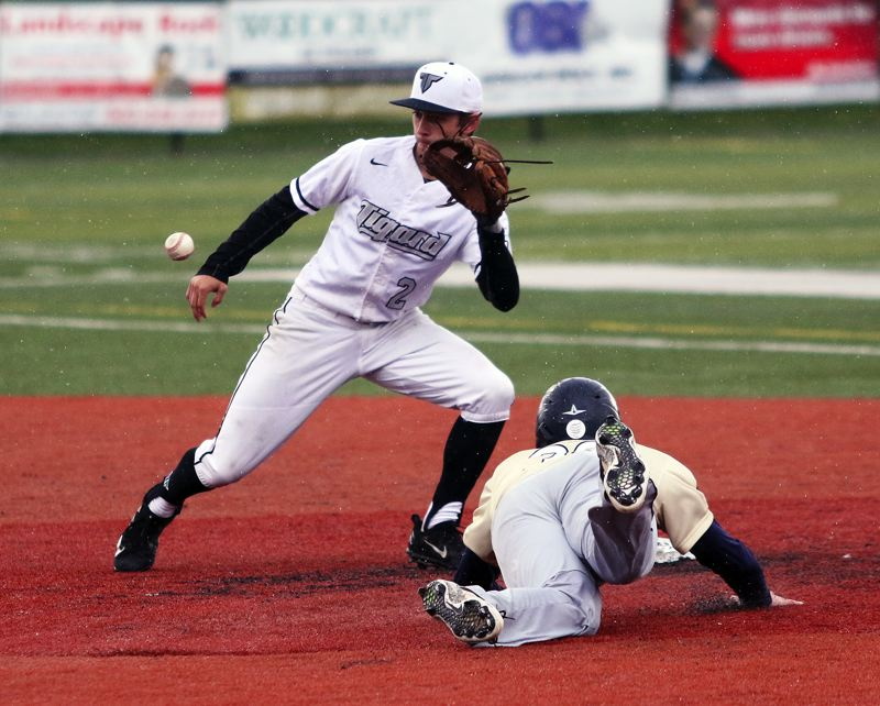 TIMES PHOTO: DAN BROOD - Tigard senior shortstop Michael Quintana (left) looks to grab the ball on a stolen base attempt by Canbys Tyler Marsh during Fridays game.