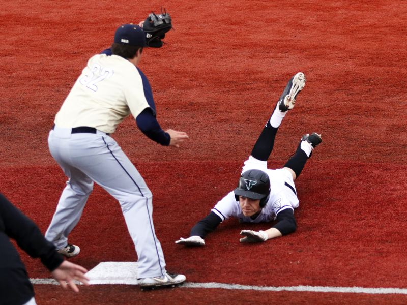 TIMES PHOTO: DAN BROOD - Tigard High School junior Lance Kreisberg (right) dives to third base safely for a fifth-inning triple during the 4-0 win over Canby.