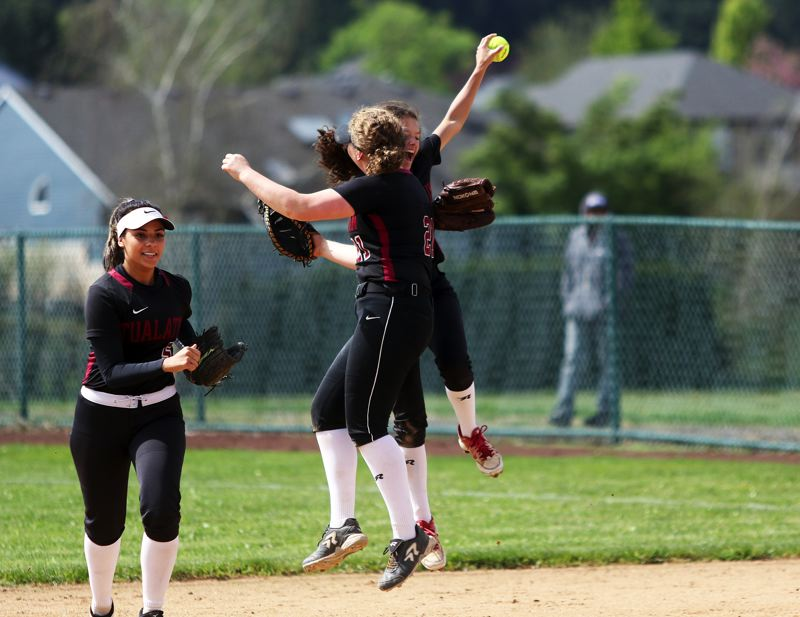 TIMES PHOTO: DAN BROOD - Tualatins (from right) Zoe Olivera, Emily Johansen and Tia Ridings celebrate following Ridings run-saving catch in the sixth inning of Saturdays game.