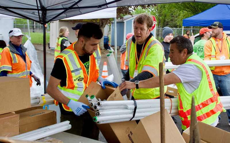 OUTLOOK PHOTO: CHRISTOPHER KEIZUR - Volunteers help unload recyclables from almost 1,100 cars during Greshams annual Earth Day Recycling Event.