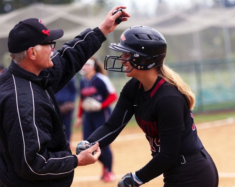 TIMES PHOTO: DAN BROOD - Tualatin freshman Taylor Corcoran is congratulated by first base coach Bill Wilson following her RBI single in the win over Westview.